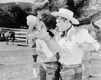 Due cowboy che combattono a vicenda (tutte le persone rappresentate non sono vivente più lungo e nessuna proprietà esiste Garanzi immagini stock libere da diritti