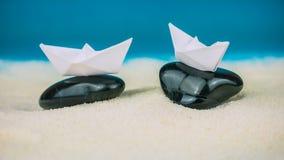 Due crogioli di Libro Bianco equilibrati sulle pietre nere che mettono su sabbia Immagini Stock