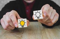 Due cubi di legno nelle mani di una persona in un vestito, uno di quale è acceso nel giallo, che simbolizza la nuova idea, il con fotografia stock