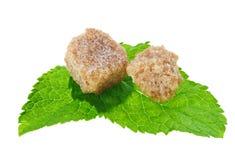 Due cubi marroni dello zucchero di canna del grumo sopra menta peperita Fotografia Stock Libera da Diritti
