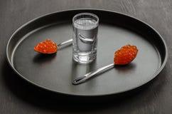 Due cucchiai con il caviale ed il vetro rossi di vodka Fotografie Stock