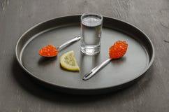 Due cucchiai con il caviale rosso, il vetro di vodka e la fetta del limone Immagine Stock