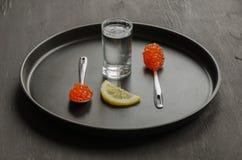 Due cucchiai con il caviale rosso, il vetro di vodka e la fetta del limone Fotografia Stock Libera da Diritti