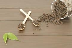 Due cucchiai di legno con le foglie di tè ed il barattolo con le foglie di tè Immagine Stock Libera da Diritti