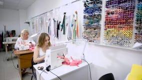 Due cucitrici femminili che lavorano alla macchina per cucire che si siede alle tavole nell'adattamento dello studio Needlewomen  stock footage
