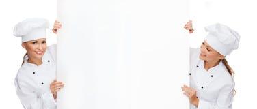 Due cuochi unici femminili sorridenti con il bordo in bianco bianco fotografie stock libere da diritti