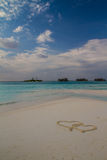 Due cuori assorbiti la sabbia alla spiaggia tropicale Fotografie Stock Libere da Diritti