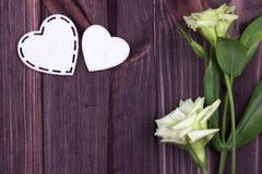 Due cuori bianchi di feltro e dei fiori su un fondo di legno marrone Giorno del biglietto di S Cartolina d'auguri nozze Fotografia Stock Libera da Diritti