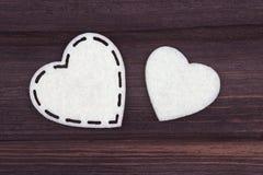 Due cuori bianchi di feltro su un fondo di legno marrone Giorno del biglietto di S Cartolina d'auguri Fotografie Stock Libere da Diritti