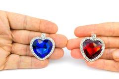 Due cuori dei gioielli a disposizione dell'uomo e della donna Fotografia Stock