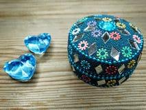 Due cuori della gemma amano e contenitore di regalo orientale su fondo di legno Fotografie Stock