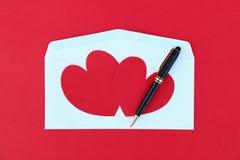 due cuori di carta rossi sulla busta bianca e sulla penna nera di affari immagini stock libere da diritti