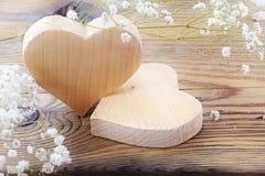 Due cuori di legno su fondo, sui biglietti di S. Valentino o sulle madri di legno d Immagine Stock