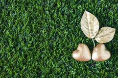 Due cuori dorati e foglie dorate sul fondo di vetro verde L Immagine Stock Libera da Diritti