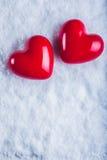 Due cuori lucidi rossi su un fondo bianco gelido della neve Amore e concetto del biglietto di S Fotografie Stock