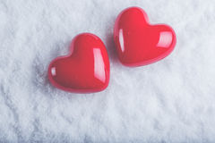 Due cuori lucidi rossi su un fondo bianco gelido della neve Amore e concetto del biglietto di S Immagini Stock