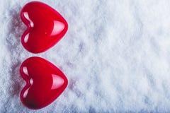 Due cuori lucidi rossi su un fondo bianco gelido della neve Amore e concetto del biglietto di S Immagine Stock Libera da Diritti