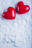 Due cuori lucidi rossi su un fondo bianco gelido della neve Amore e concetto del biglietto di S Fotografia Stock