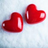 Due cuori lucidi rossi su un fondo bianco gelido della neve Amore e concetto del biglietto di S Immagine Stock