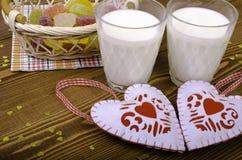 Due cuori, marmellata d'arance in un canestro di vimini e due bicchieri di latte Fotografia Stock