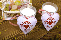 Due cuori, marmellata d'arance in un canestro di vimini e due bicchieri di latte Fotografia Stock Libera da Diritti