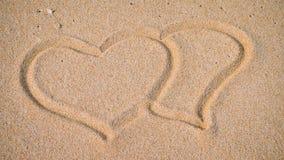 Due cuori nella sabbia sulla spiaggia Fotografia Stock
