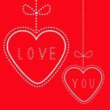 Due cuori rossi d'attaccatura con gli archi. Carta di amore. Immagine Stock