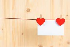 Due cuori rossi decorativi con la cartolina d'auguri che appende sul fondo di legno, concetto del giorno di S. Valentino Fotografie Stock