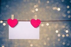 Due cuori rossi decorativi con la cartolina d'auguri che appende sul fondo leggero blu e dorato del bokeh, concetto del giorno di  Immagine Stock Libera da Diritti