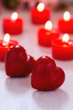 Due cuori rossi e candele brucianti sulla tavola immagini stock libere da diritti