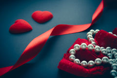 Due cuori rossi luminosi con i nastri e le perle rossi Fotografia Stock