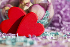 Due cuori rossi luminosi su un fondo delle rose secche e del lamé di carta Immagini Stock