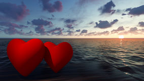 Due cuori rossi nel mare al tramonto Fotografia Stock Libera da Diritti