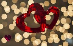 Due cuori rossi sono intrecciati e messi contro un fondo delle luci di twinkling immagine stock