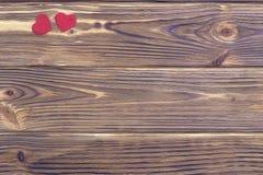 Due cuori rossi su fondo di legno marrone Fotografie Stock