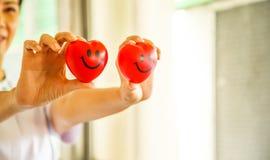 Due cuori sorridenti rossi hanno tenuto dalle mani femminili del ` s dell'infermiere, rappresentanti dando la mente di servizio d immagine stock