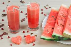 Due cuori, succo dell'anguria in due tazze di vetro con una paglia su un fondo di legno leggero, un cocktail delizioso, a Fotografie Stock