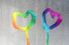 Due cuori sui precedenti di vetro con le gocce, tinte nei colori dell'arcobaleno Immagini Stock Libere da Diritti