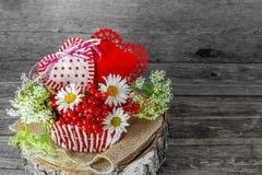 Due cuori in un canestro di vimini con le bacche ed i fiori il giorno del ` s del biglietto di S. Valentino in uno stile rustico fotografie stock libere da diritti
