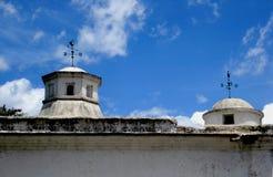 Due cupole da una vecchia costruzione e da un cielo blu in Antigua Guatemala immagine stock