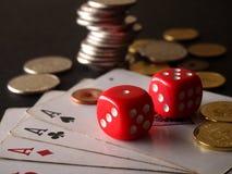 Due dadi, carte del gioco e pile rossi di monete Fotografia Stock