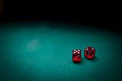 Due dadi rossi su una tabella di scheda Immagini Stock