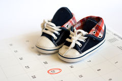 Due date in the calendar and detail of baby shoes Stock Photo