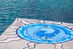 Due delfini dipinti su un pavimento di pietra nell'oceano di Subic avventurano Fotografie Stock