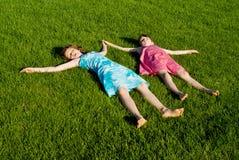 Due delle ragazze hanno dormito sull'erba fotografia stock
