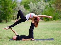 Due di yoga di pratica della donna all'aperto Posa di yoga di Acro Immagine Stock