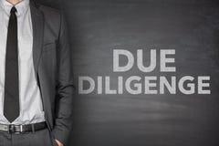 Due diligence on blackboard. Due diligence on black blackboard with businessman Stock Photo