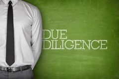 Due diligence text on blackboard. Accounting concept on blackboard with businessman standing side Royalty Free Stock Images