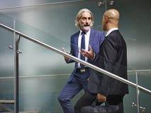 Due dirigenti aziendali che parlano mentre scale salenti Fotografia Stock Libera da Diritti