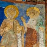 Due discepoli con i testi latini in un affresco medievale Immagini Stock